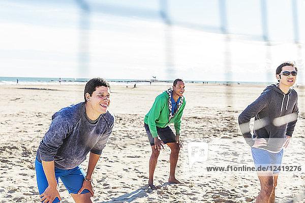 Men playing beach volleyball on sunny beach