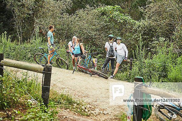 Friends mountain biking  resting on trail