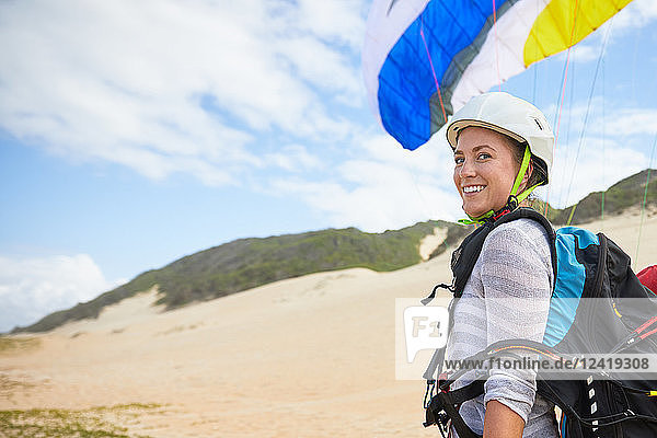 Portrait smiling,  confident young female paraglider on beach