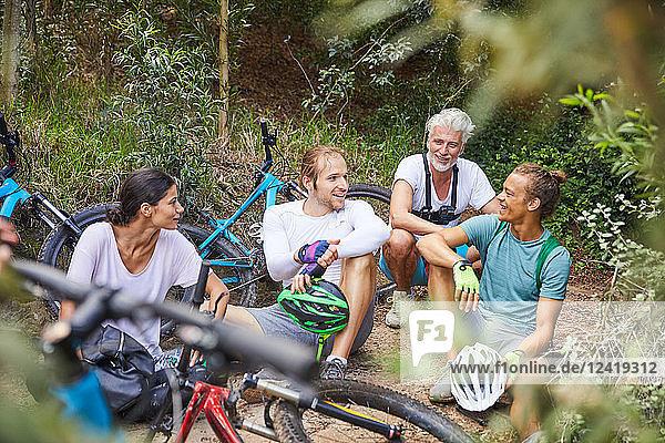 Friends mountain biking  resting in woods