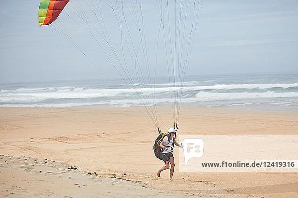 Male paraglider running on ocean beach