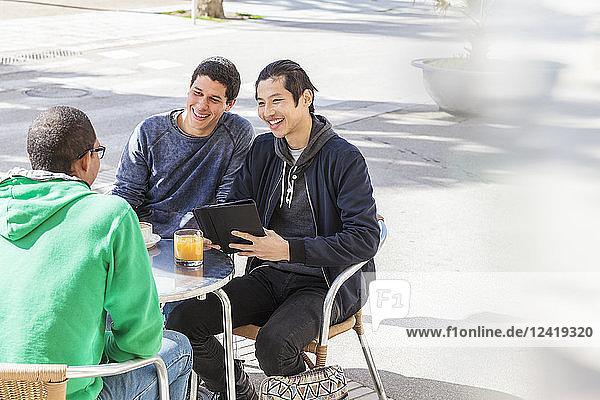 Smiling male friends talking at sunny sidewalk cafe