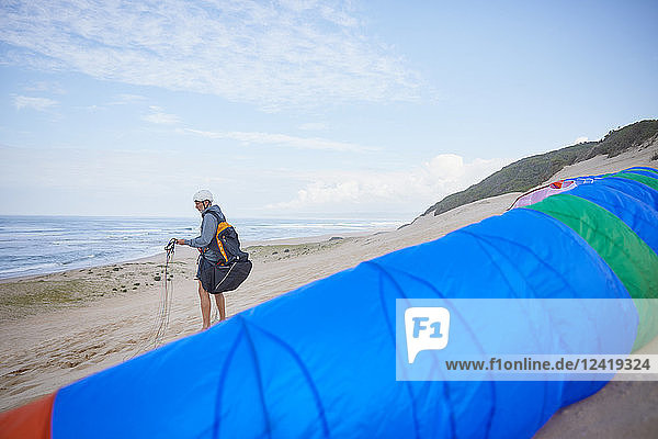 Male paraglider with parachute on ocean beach
