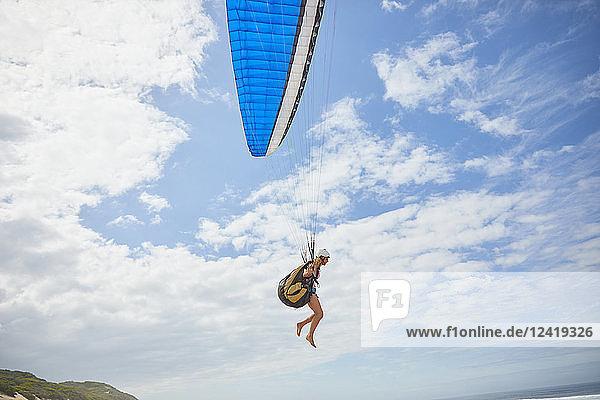 Female paraglider paragliding against sunny blue sky