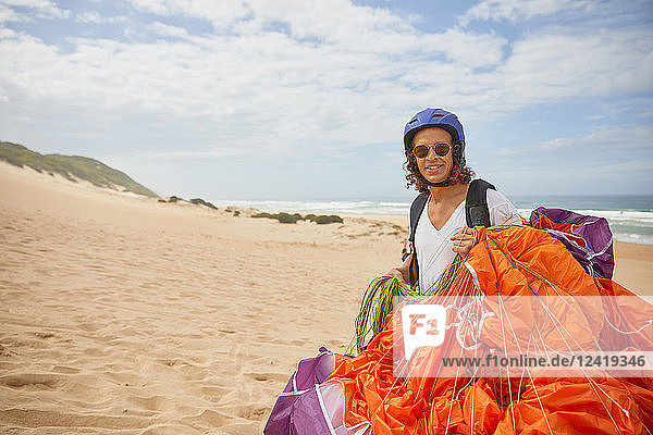 Portrait smiling male paraglider with parachute on beach