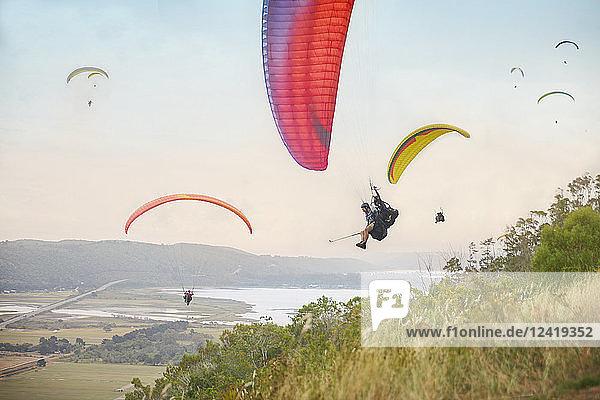 Paragliders in sky over landscape