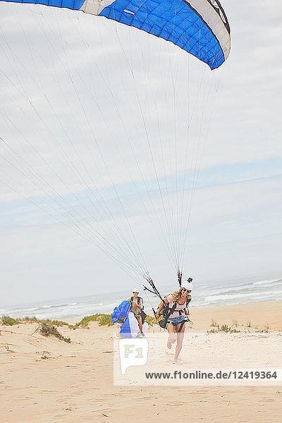 Female paraglider with parachute on ocean beach