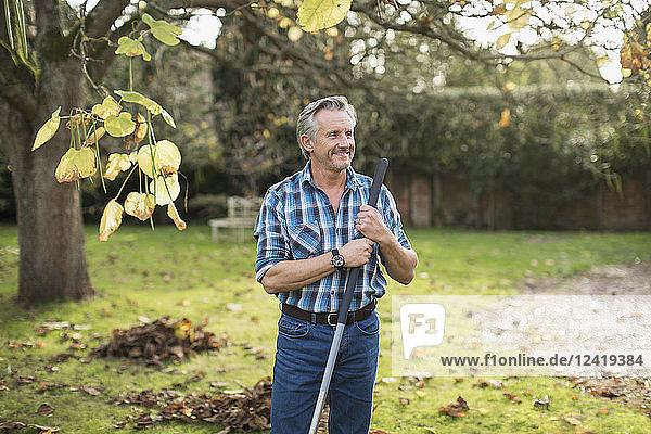 Smiling senior man raking autumn leaves in backyard