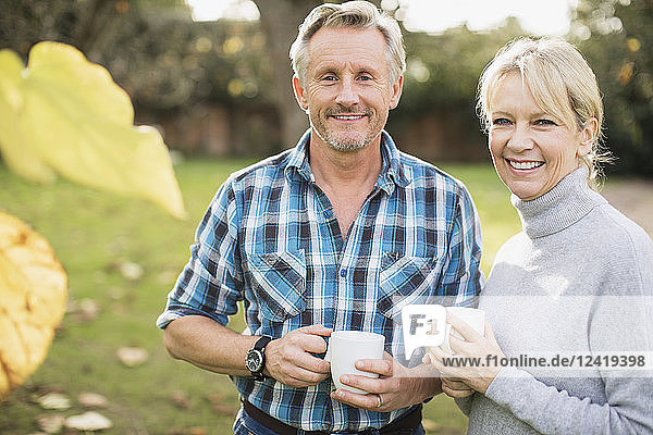 Portrait smiling  confident mature couple drinking coffee in autumn yard