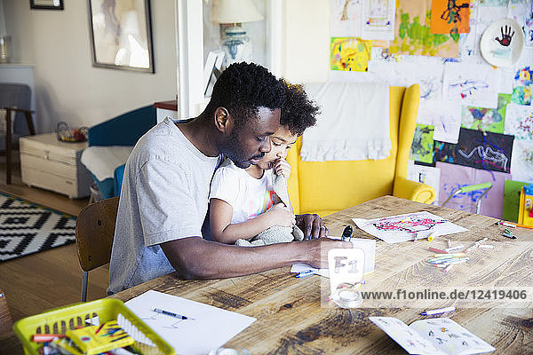 Father and toddler daughter coloring at table