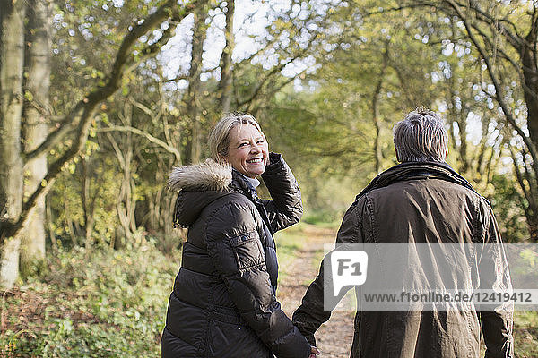 Portrait smiling  carefree mature couple holding hands  walking in sunny autumn woods