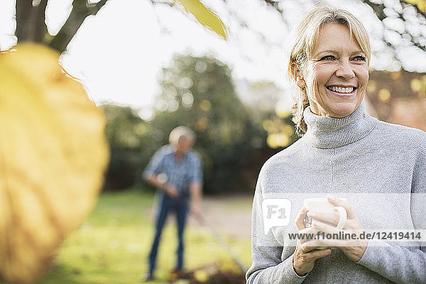 Portrait smiling  happy mature woman drinking coffee in autumn yard