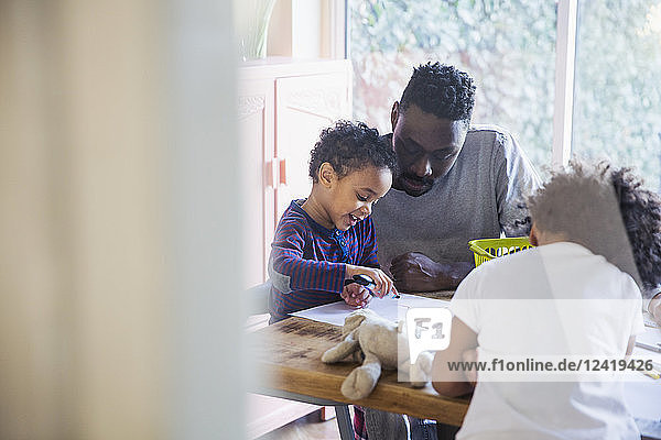 Father and toddler son coloring at table