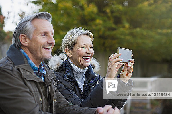 Happy mature couple using camera phone in park