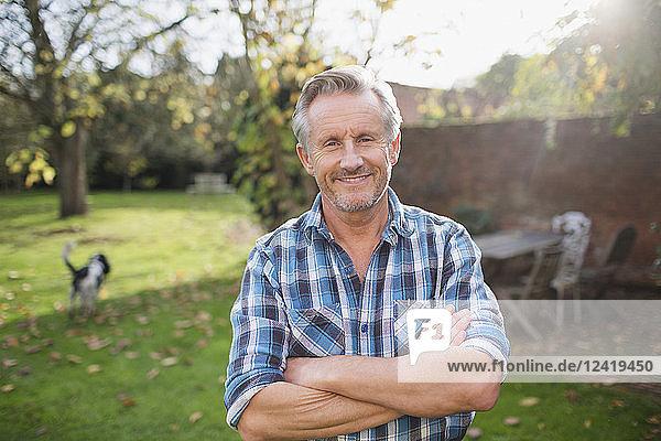 Portrait confident senior man in sunny autumn backyard