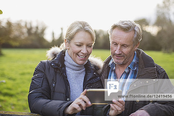 Mature couple taking selfie with smart phone in park