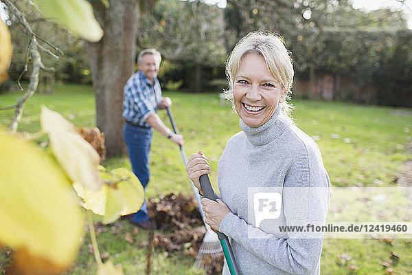 Portrait smiling  confident mature woman raking autumn leaves in backyard