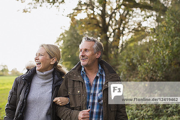 Happy mature couple walking arm in arm in autumn park