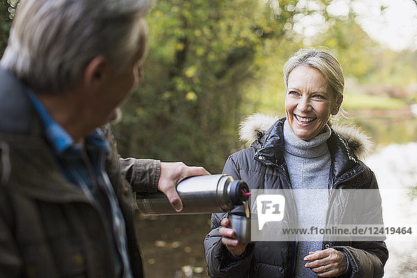 Happy mature couple drinking coffee from insulated drink container in autumn park