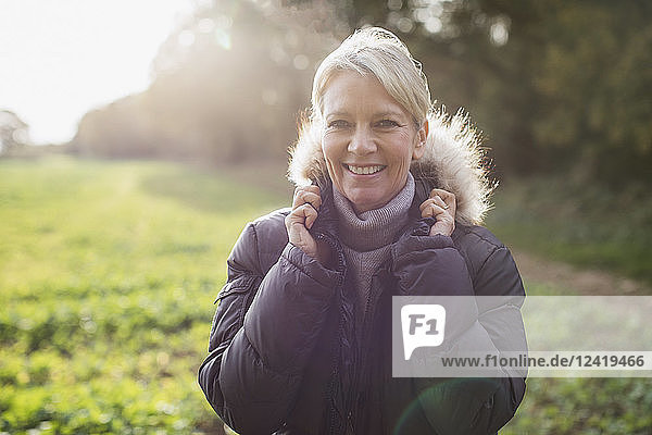 Portrait smiling  confident mature woman in parka in sunny park