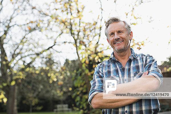 Portrait confident mature man in autumn backyard