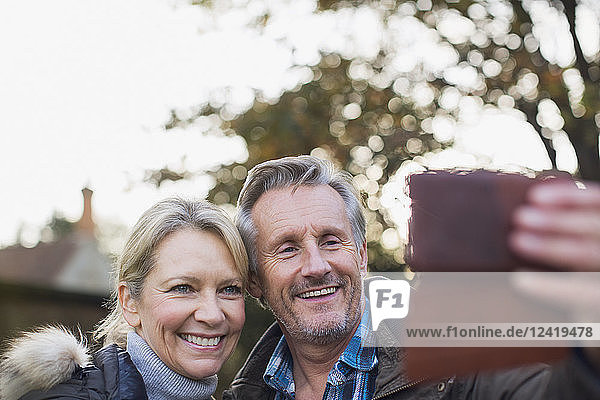 Smiling,  happy mature couple taking selfie with camera phone