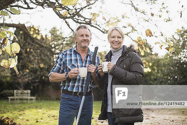 Smiling mature couple drinking coffee and raking autumn leaves in backyard