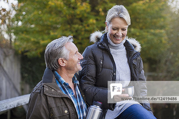 Mature couple drinking coffee in park