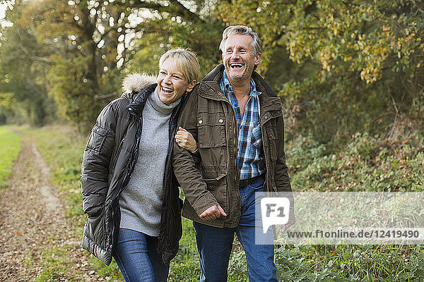 Happy  carefree mature couple walking arm in arm in autumn park