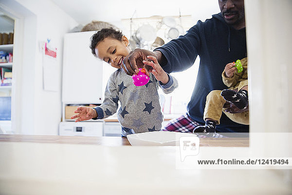 Father and children playing in kitchen