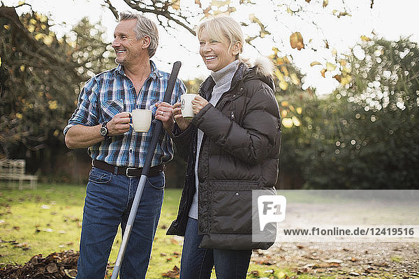 Mature couple drinking coffee and raking autumn leaves in backyard