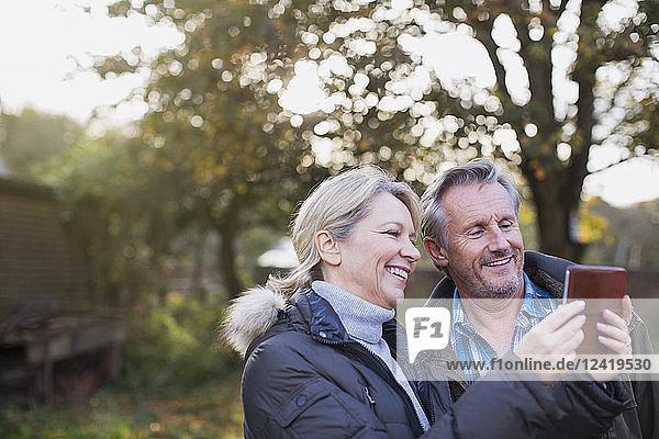 Mature couple using smart phone in autumn backyard