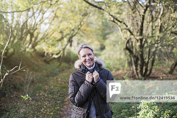 Portrait confident mature woman in parka in sunny autumn woods