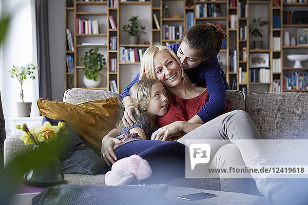 Mother and her daughters cuddling and having fun  sitting on couch
