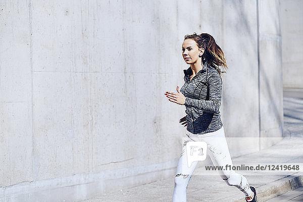 Female runner  concrete wall