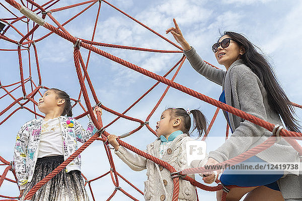 Mother with two daughters in climbing frame