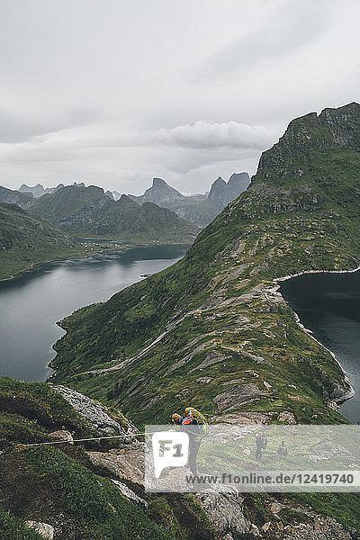 Norway  Lofoten  Moskenesoy  Group of young men hiking at Vinstad