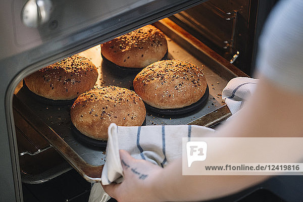Woman taking homemade vegan burger rolls out of oven