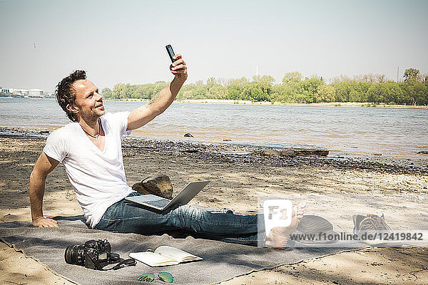 Smiling man sitting on blanket at a river taking a selfie