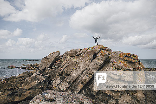 France  Brittany  Meneham  man standing on rock formation at the coast