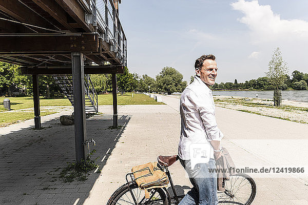 Mature man with bike at Rhine riverbank