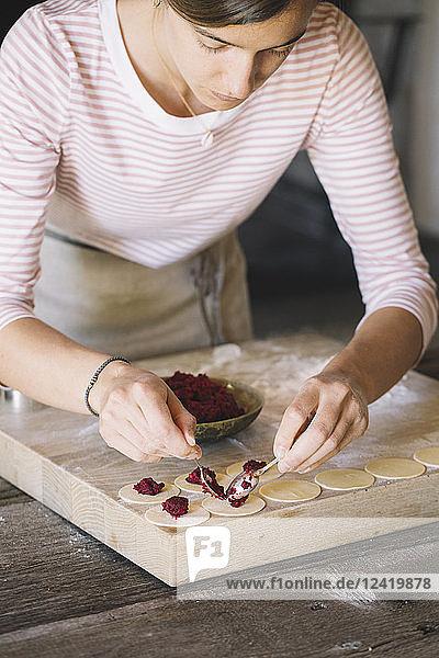 Woman preparing ravioli  beetroot sage filling