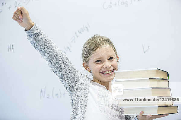 Portrait of happy schoolgirl carrying books in class