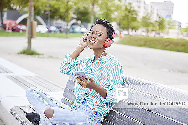 Portrait of young woman sitting on bench listening music with cell phone and headphones Portrait of young woman sitting on bench listening music with cell phone and headphones