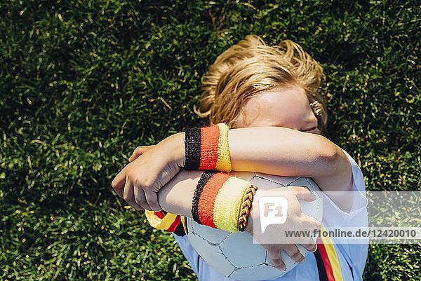 Boy in German soccer shirt lying on grass  hugging ball