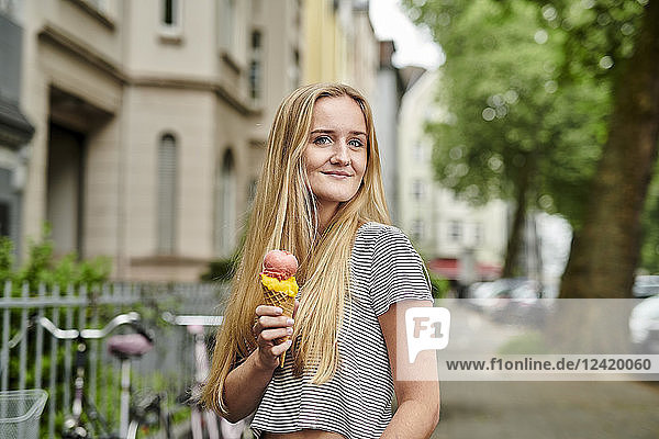 Young woman enjoying an ice cream cone in the city