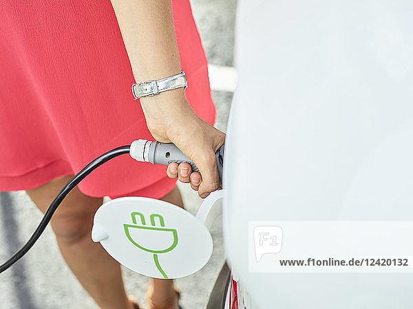 Close-up of woman charging electric car Close-up of woman charging electric car