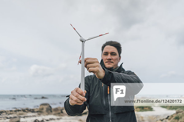France  Brittany  Meneham  man with miniature wind turbine at the coast