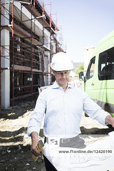 Architect with blueprint wearing hard hat on construction site