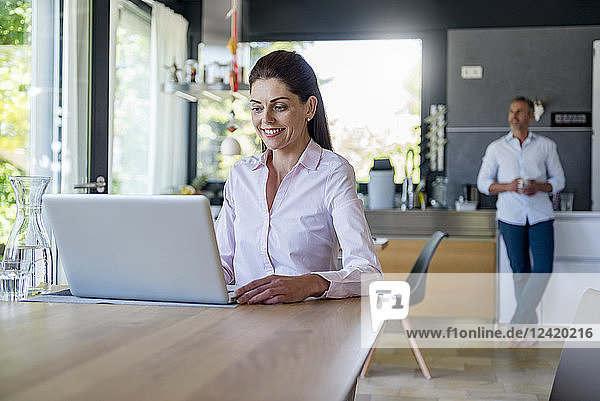 Smiling woman at home using a laptop at table with man in background